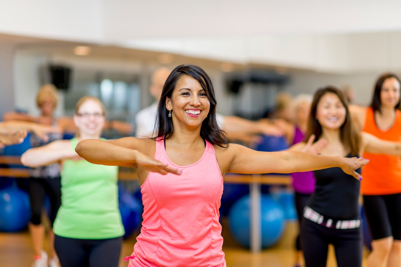 A woman is leading out in a fitness dance class at her indoor studio. She is teaching a multi-ethnic class that is wearing fitness clothing and dancing to the music.
