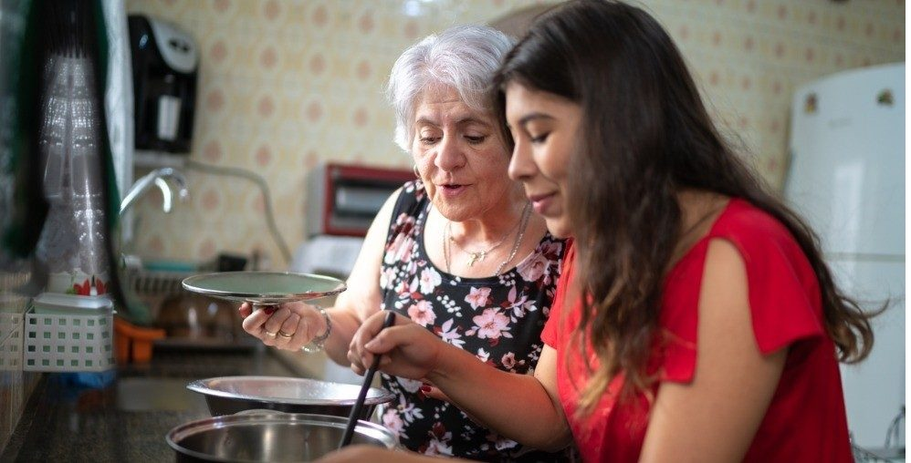 Grandmother teaching her granddaughter how to cook