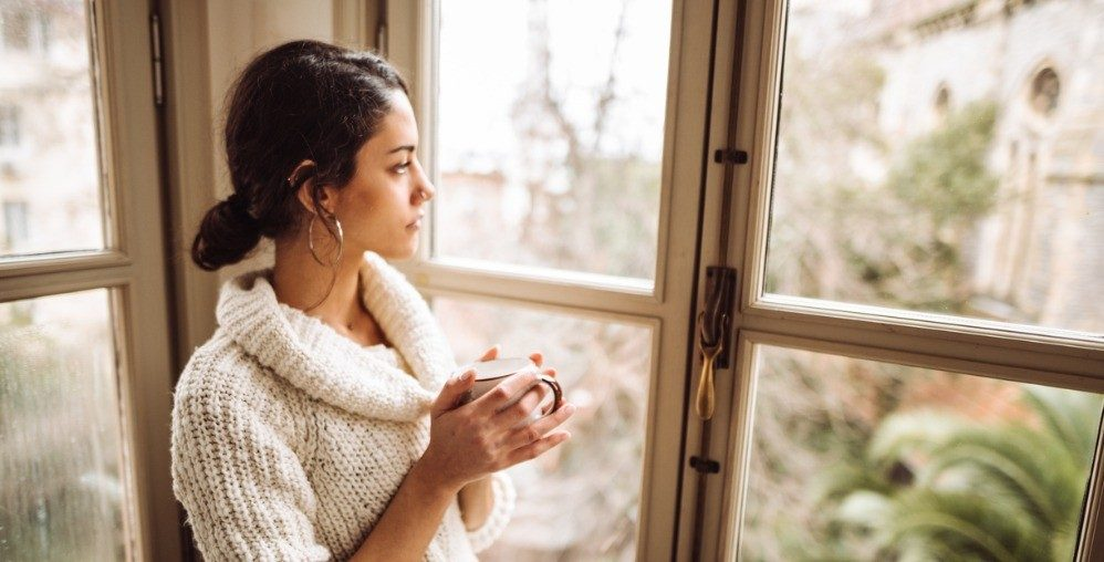 Woman with coffee looking out window