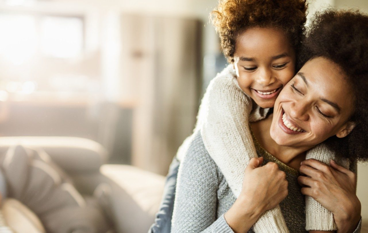 Happy black girl embracing her mother with great affection at home. Copy space.