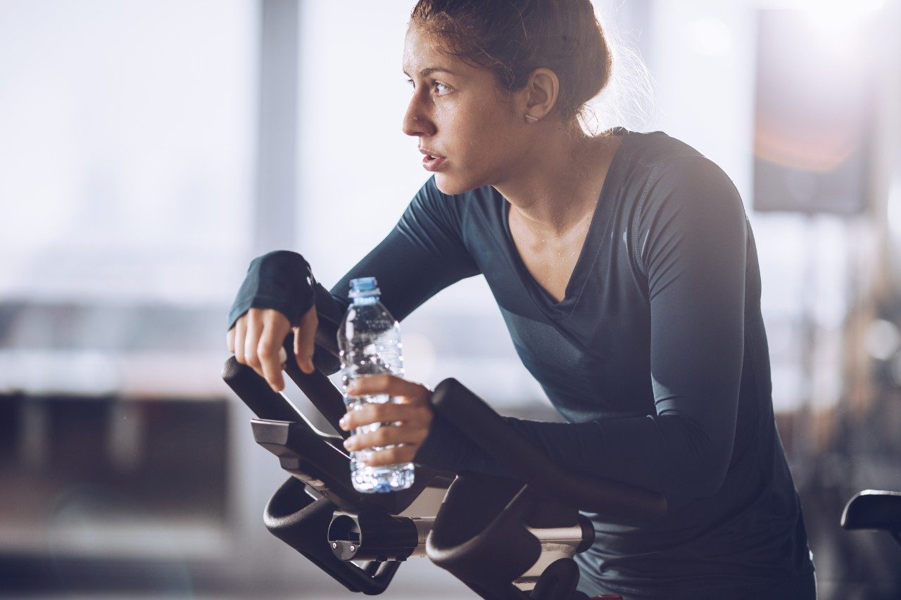 Tired sportswoman having a water break during exercising class in a health club.