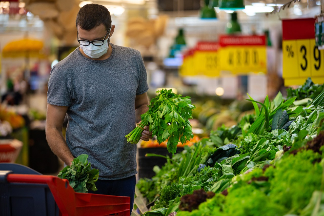 Alarmed male wears medical mask against coronavirus while grocery shopping in supermarket or store- health, safety and pandemic concept - young man wearing protective medical mask for protection from virus covid-19 and stockpiling food